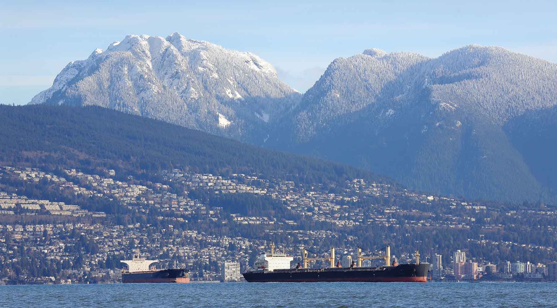 cargo vessel waiting in vancouver port with mountains in the background